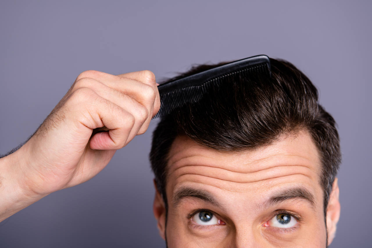 A close up of a man combing his hair and thinking on how to increase his hair volume