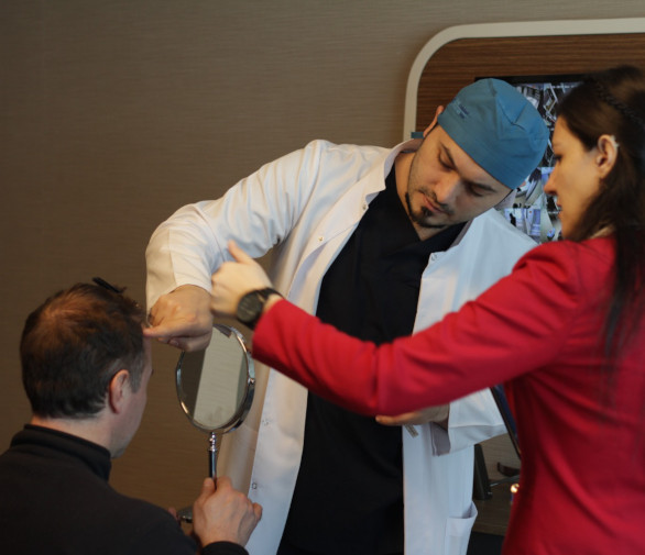 Dr Balwi analysing his patients hair before their hair transplant