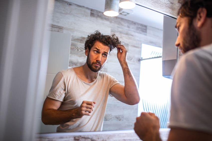 Man applying hair care products to his hair at home