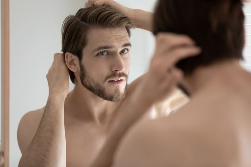 Man touching his hair after a successful hair transplant