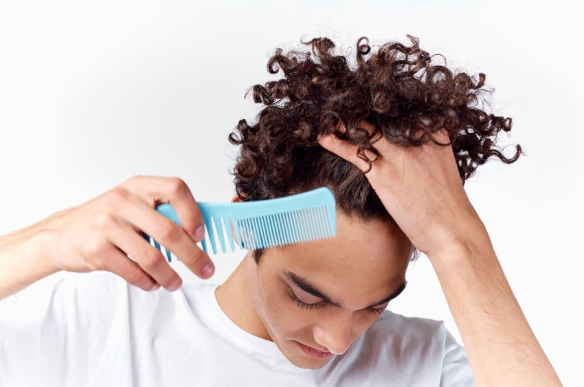 Man with curly hair looks at his receding hair line