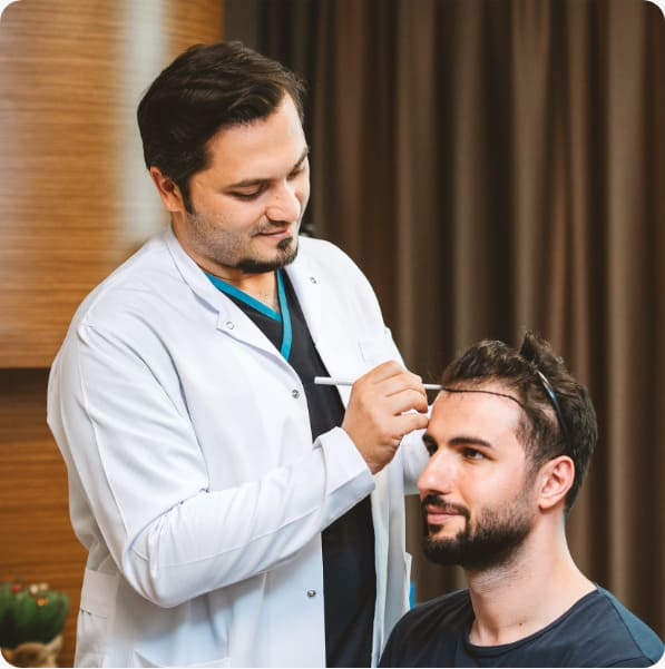 Dr. Balwi examines the scalp and designs a patient's new hairline before his hair transplant at Elithair