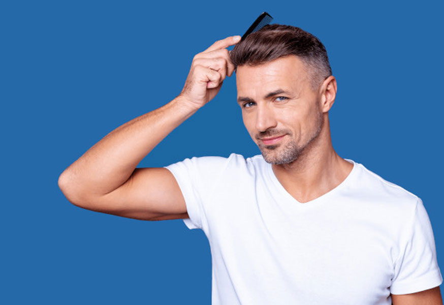A man styling his hair after his hair transplant results