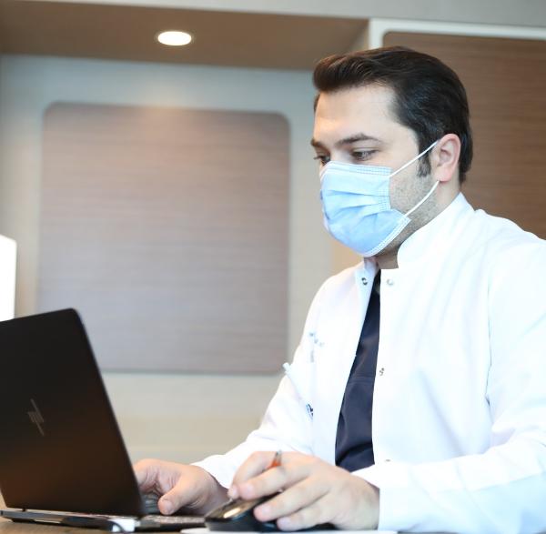 Hair transplant surgeon Dr Balwi working on his laptop