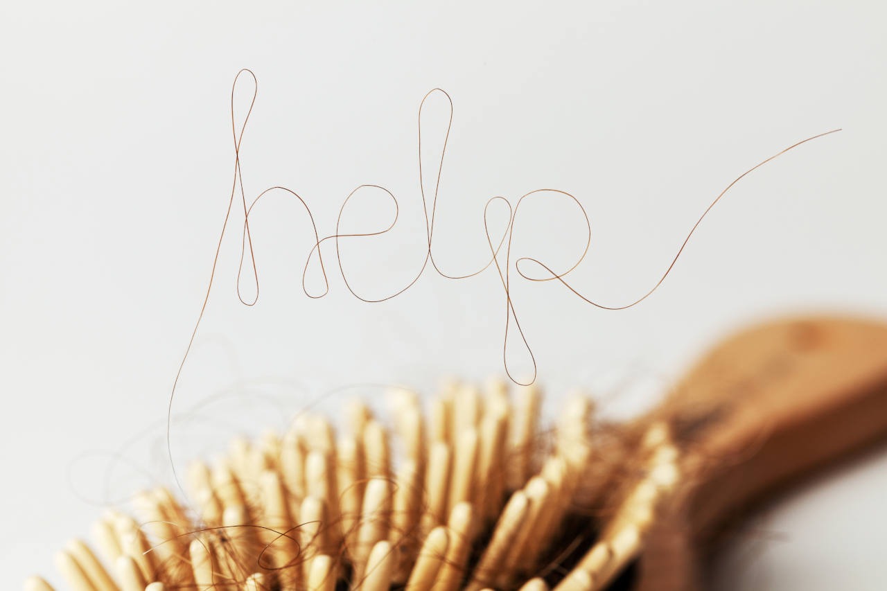 A strand of hair on a hairbrush spelling help
