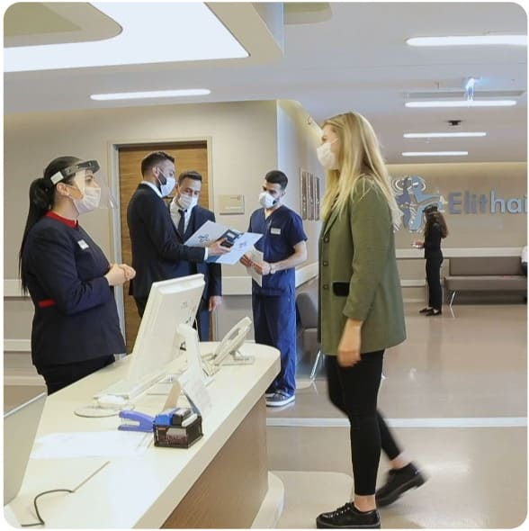 A woman is greeted at the reception desk during corona